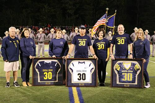 Group of people standing with three football jerseys each displayed in frames.